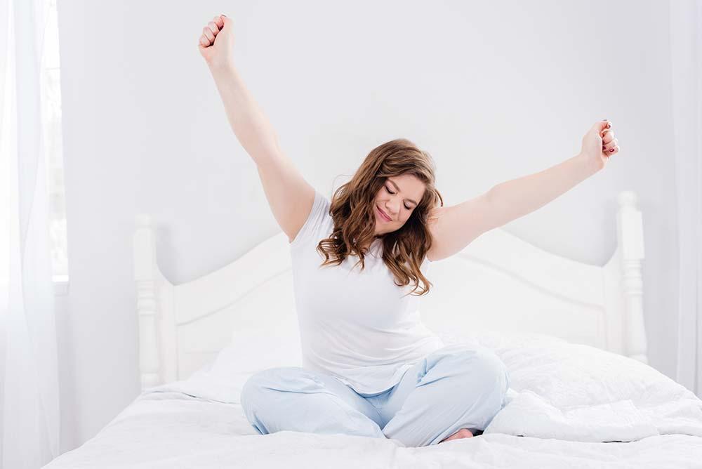 mujer en pantalones cortos y camiseta en la cama