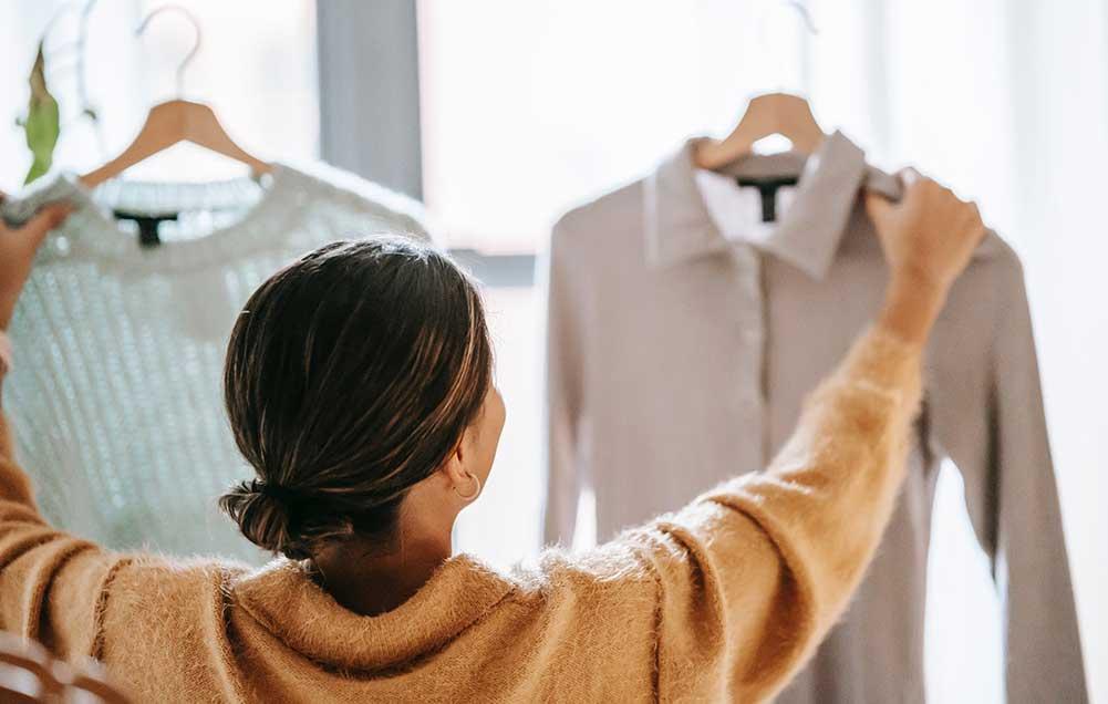 mujer recogiendo una camisa del armario