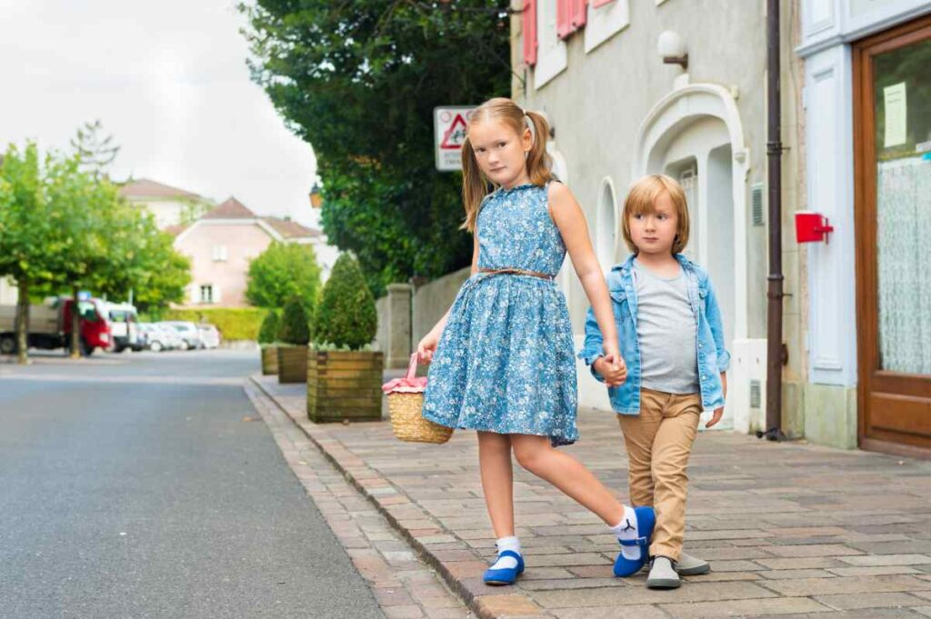 2 kids with blue tops in the street